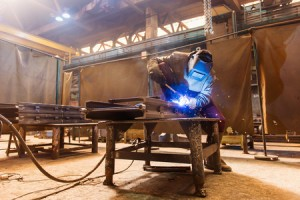 39484833 - young man with protective mask welding in a factory